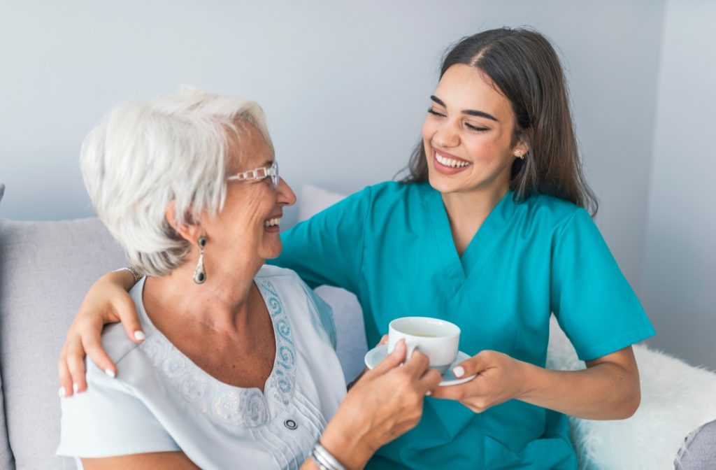 Happy nurse at senior community handing over cup of tea to smiling senior woman.